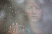 Teenage girl looking out a rainy window pane.
