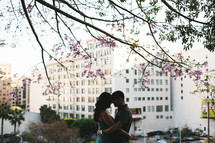 couple hugging and a city in a background