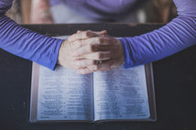 A woman's hands folded in prayer on an open Bible