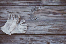 Work gloves laying on rustic boards.