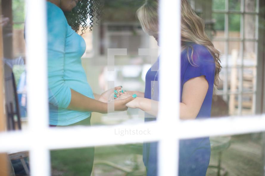 Women holding hands in prayer inside a window.