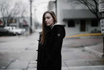a young woman walking down a street and looking back at the camera