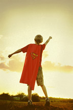 Boy with cape pretending to take off