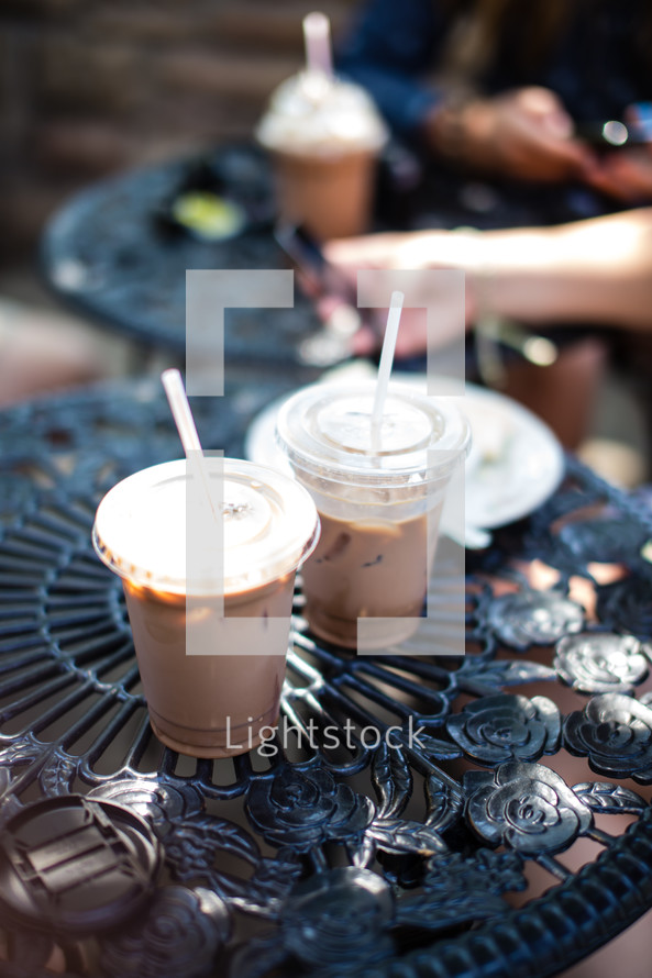 Iced coffee drinks in plastic cups on table at an outdoor bistro cafe.