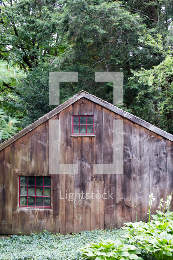 Wooden barn in the trees.