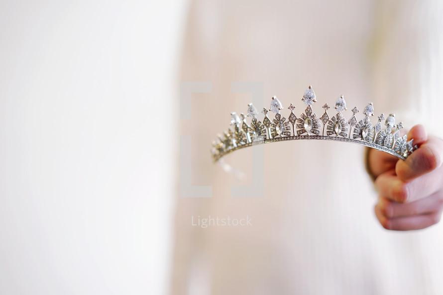 a woman holding tiara