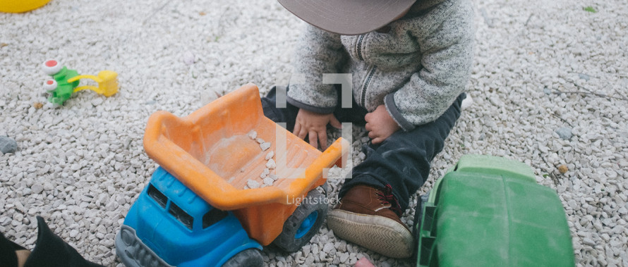 toddler boy playing in gravel with a toy dump truck