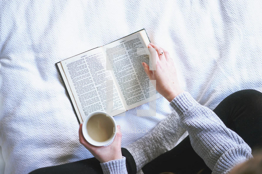 a girl sitting on a bed reading a Bible