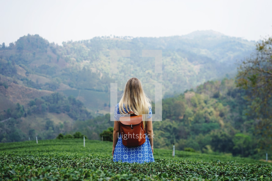 a woman standing in a vineyard