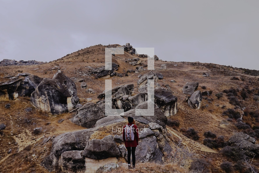 woman backpacking over a rocky terrain
