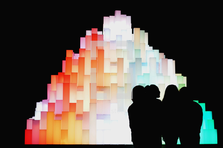 silhouettes standing in front of a glowing rainbow sculpture