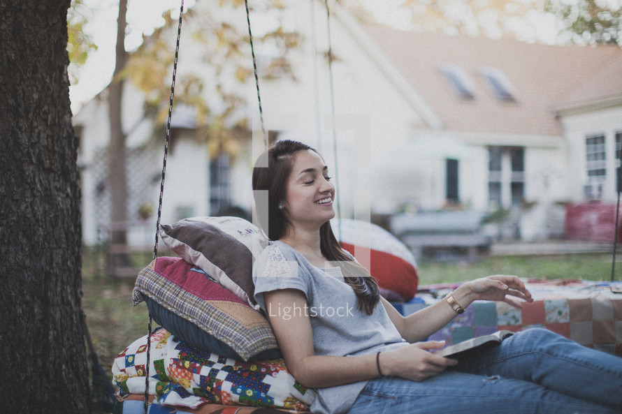 A young woman sitting on a swing laughing and reading the Bible