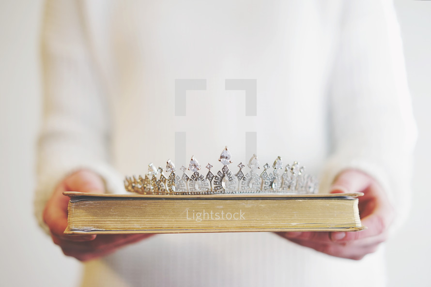 a woman holding a tiara and Bible