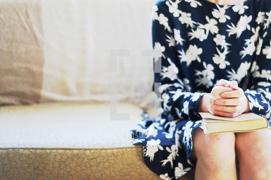 teen girl praying over a Bible in her lap