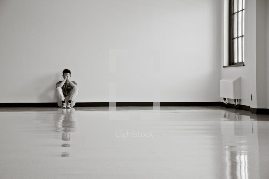 a sad man sitting against a wall
