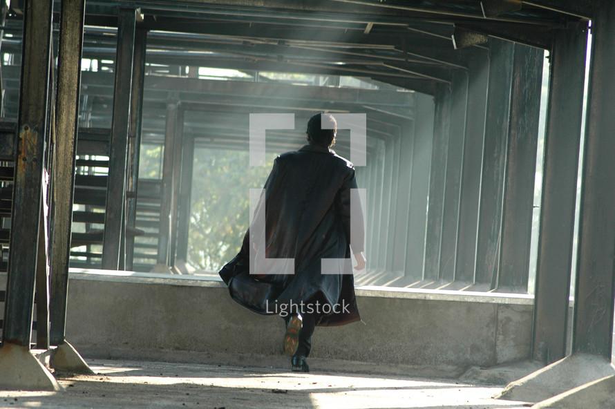 man in a trench coat walking in sunlight