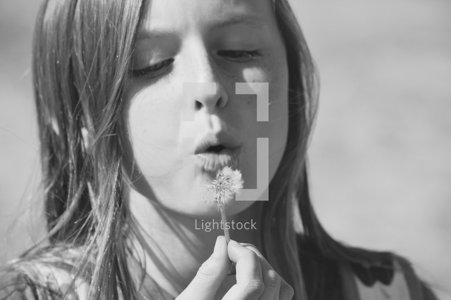 a girl blowing on a dandelion