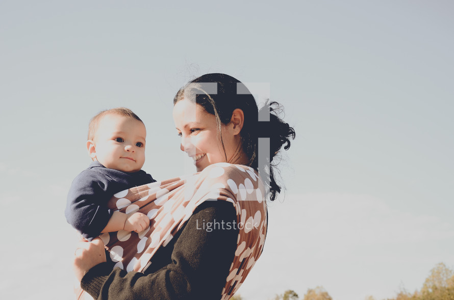 Woman smiling while holding a baby