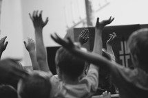 children with raised hands singing to worship music at VBS