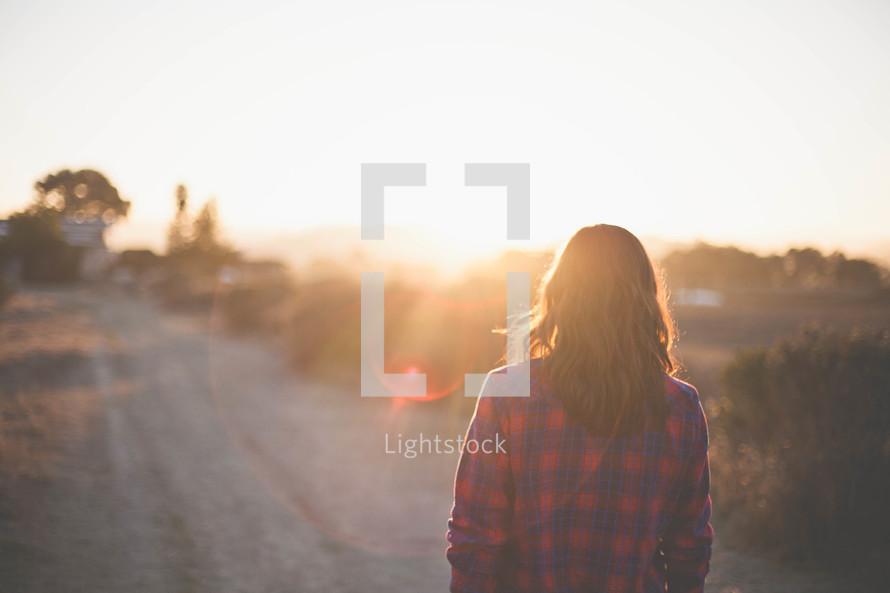A woman walking on a dirt road under intense sunlight