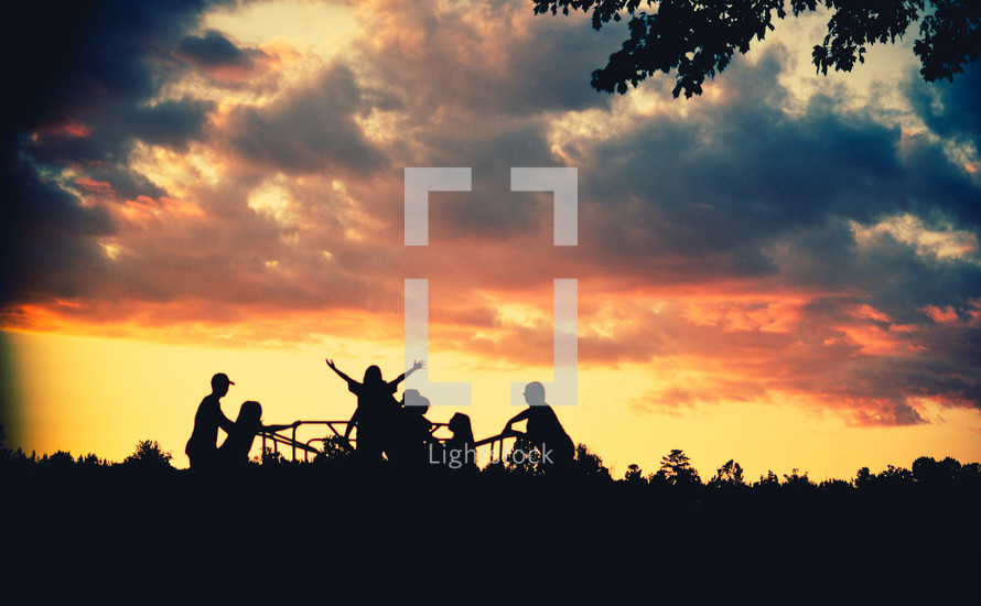 silhouettes of children playing on a playground at sunset