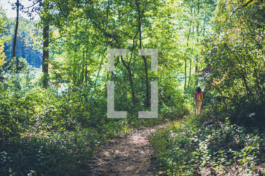 woman walking on a trail leading to a lake