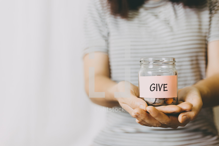 person holding a give jar