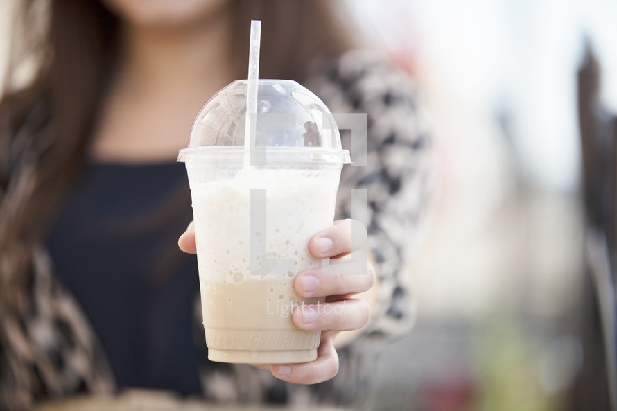 woman holding a milkshake