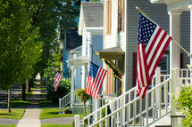 American flags on front porches of houses in a row.