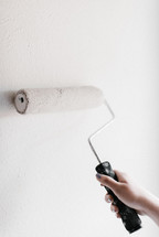 Paint being rolled onto a wall.