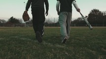 men walking on a baseball field carrying bats and gloves