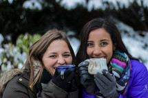 women with mugs standing outdoors in winter