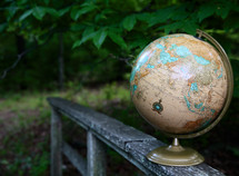 globe on a weathered railing