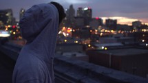 man standing on a roof looking out at the city below