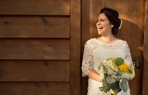 happy bride standing outside holding her bouquet