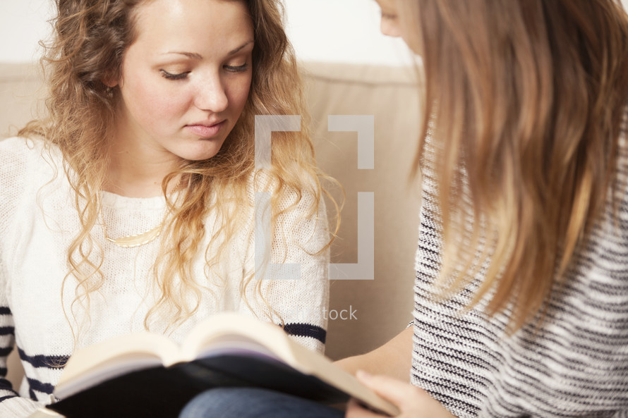 Teen friends sitting on the sofa and reading the Bible together.