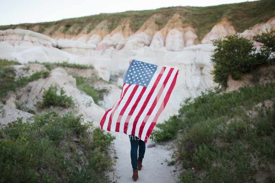 a woman walking on a trail carrying an American flag on her back