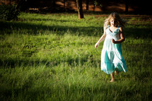 Little girl running in grass field