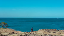 a man standing at the edge of a cliff overlooking the ocean