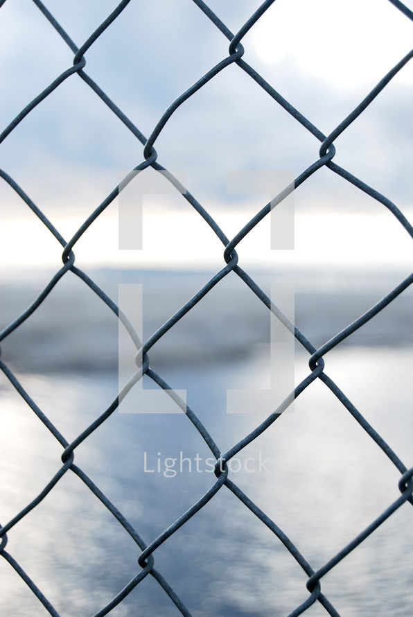 view of water through a chain link fence