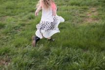 girl child running through green grass