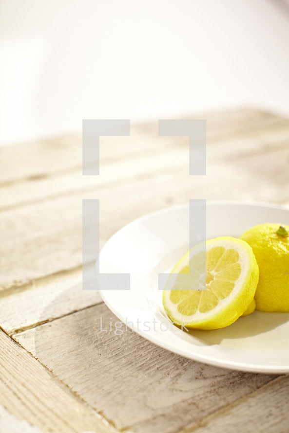 Two halves of a lemon on a white plate