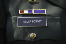"""The words """"Never Forget"""" printed on the military name badge of uniform."""