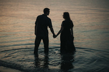 a couple holding hands standing in a pond