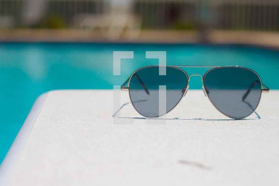 sunglasses on a pool deck