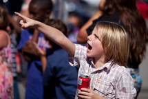 Child pointing and holding a drink