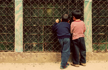 Boys looking through windows with bars
