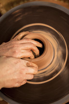 hand on clay on a potter's wheel