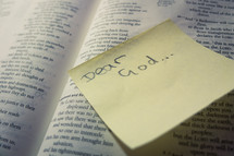 A post-it sticky note with 'Dear God' stuck to a page of an open bible