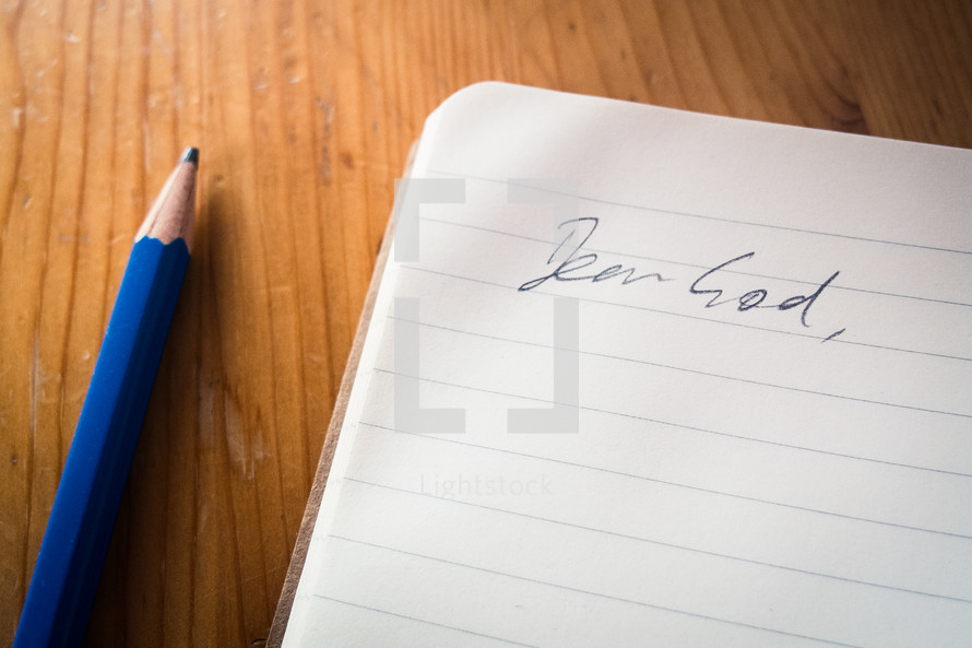 An open notebook with the words 'dear God' and a blue pencil laying beside.